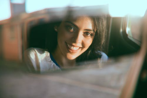 Reflection of cheerful woman in car window
