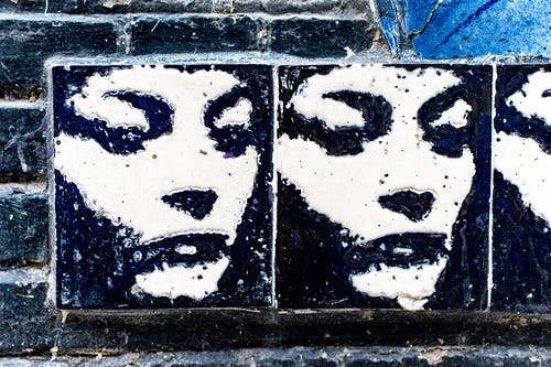 Graffiti of white and black female face on wall with black bricks in city