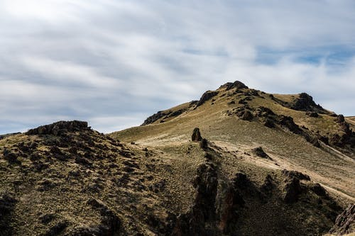 Mountainous landscape of high rocky rough steep peak under cloudy sky at daytime