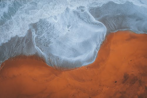 Drone view of foaming stormy clean sea waves rolling near brown sandy coastline