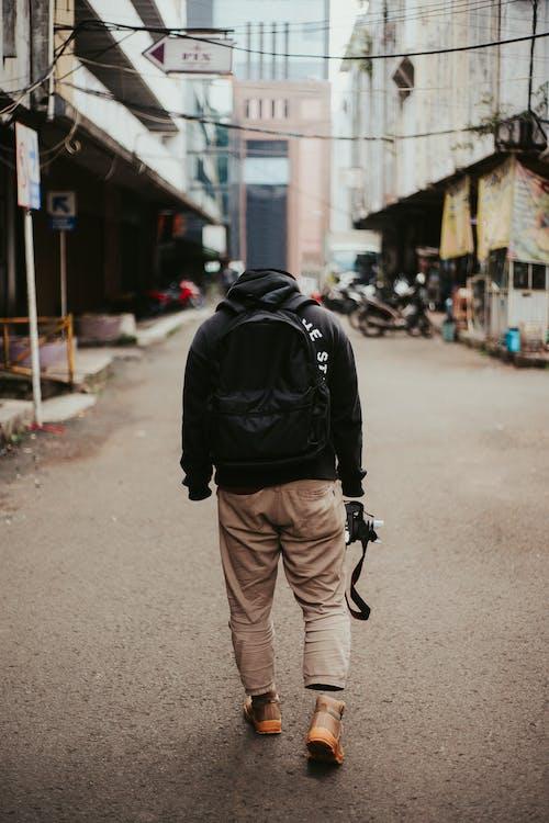 Man in Black Jacket and Brown Pants Walking on Street