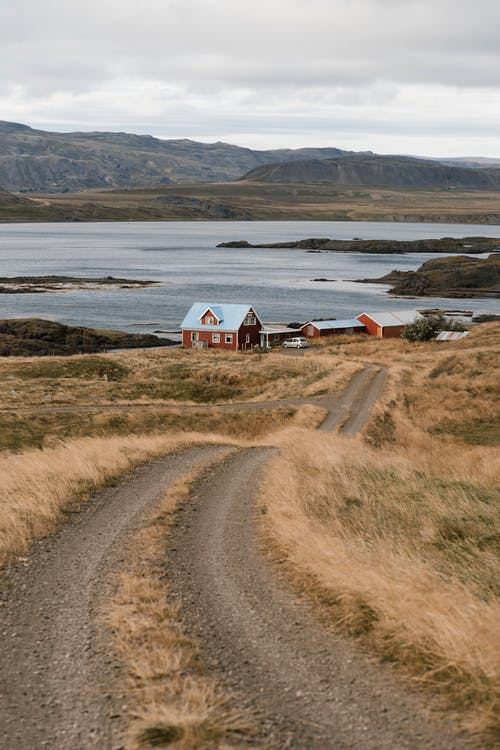 Country road to farm house placed on coastline with hilly cliffs above lake