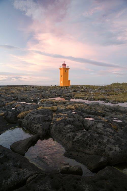 Orange beacon on seashore in daytime