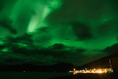 Northern lights over mountain and city