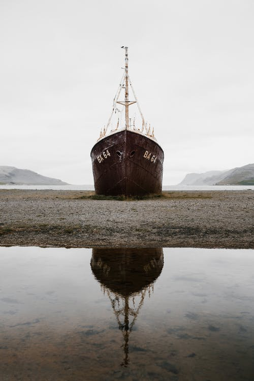 Old vessel stranded on sandy shore near mountains and lake