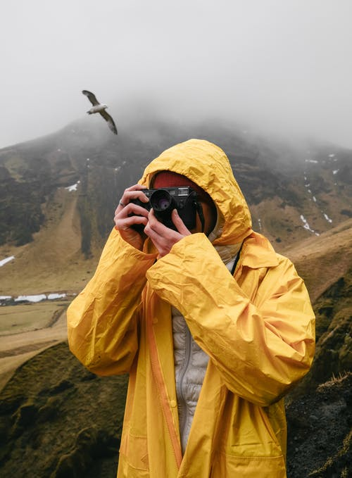 Crop unrecognizable tourist taking photo with photo camera in mist