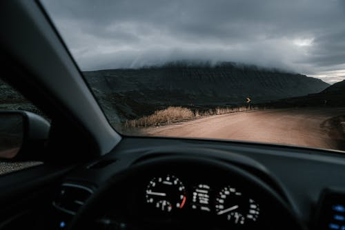 View from inside car on road in countryside near mounts and faded grass in mist under cloudy sky
