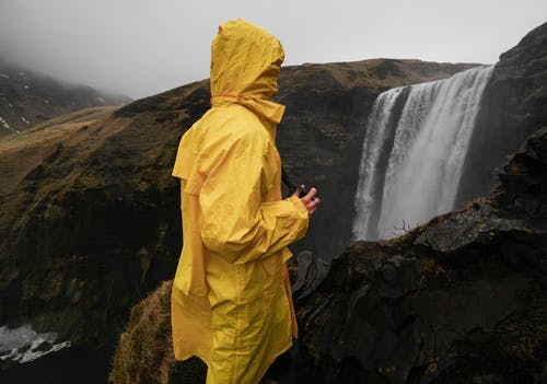 Side view of unrecognizable traveler in yellow raincoat standing on mountain close to high cascade in foggy weather in evening