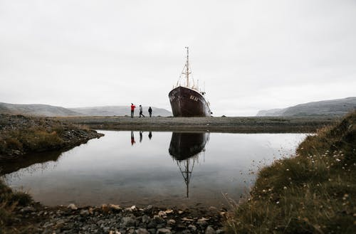 Group of tourists standing near old ship reflecting in pond