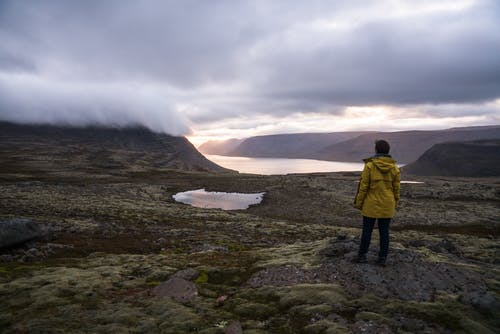 Back view of anonymous male traveler in raincoat standing in front of sea between ridge under cloudy sky in foggy weather