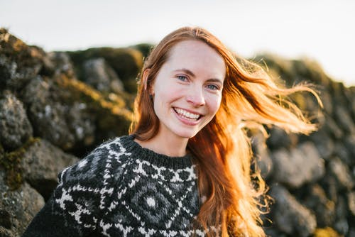 Positive ginger woman standing near stone wall in sunlight