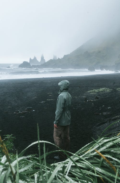 Side view of anonymous traveler in raincoat standing in front of stormy sea surrounded by ridge and grass covered with dew in foggy weather