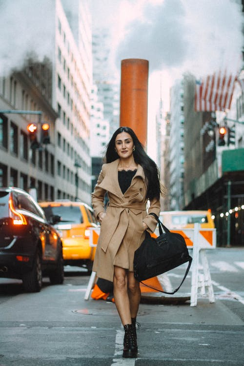 Stylish woman walking on street of busy downtown