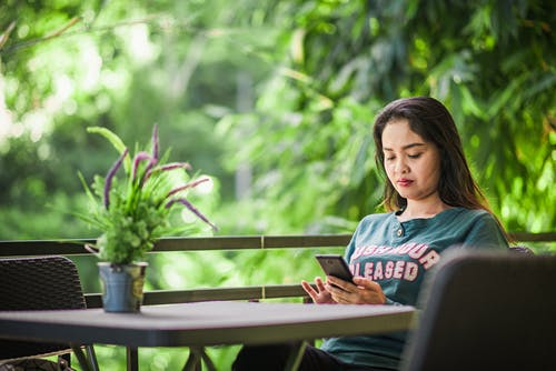 Concentrated young female freelancer browsing cellphone while working remotely in green outdoor terrace