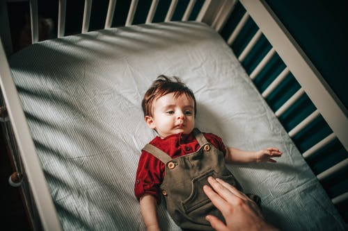 From above of faceless person pulling hand to child resting in crib in kids room