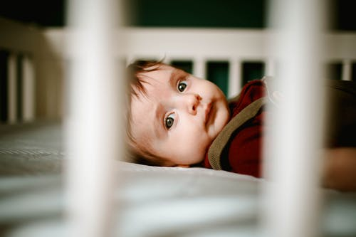 Calm baby lying in crib at home