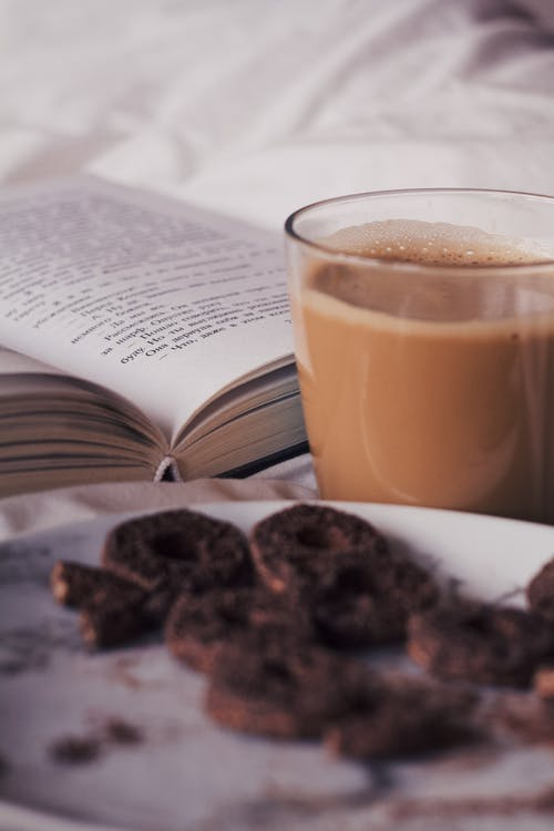 Cup of coffee with plate of cookies near book