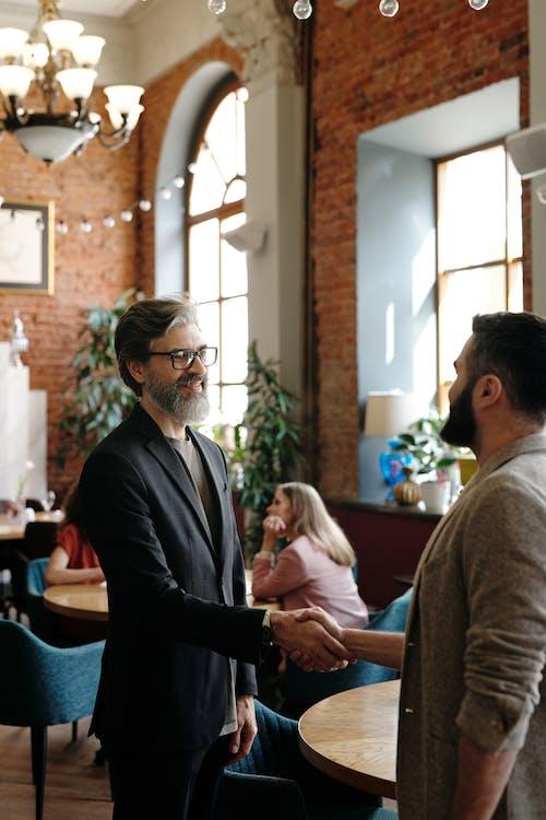 Man in Black Suit Jacket Sitting Beside Woman in Gray Long Sleeve Shirt