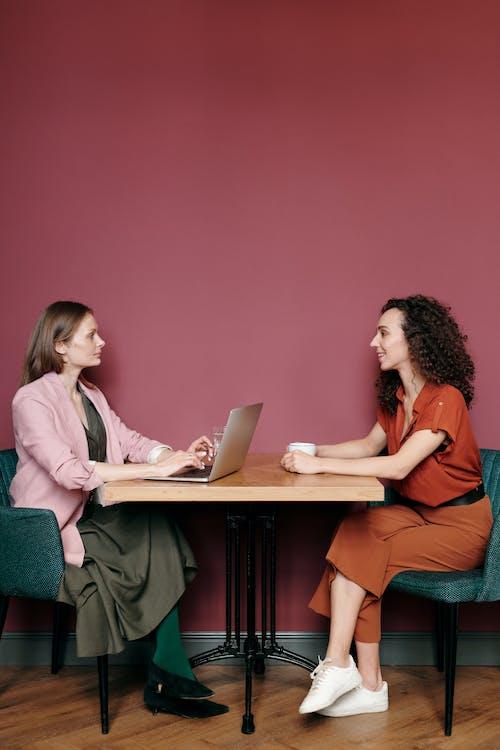 2 Women Sitting on Chair Using Macbook