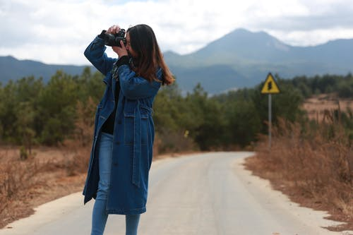 Young woman taking photos on camera in countryside