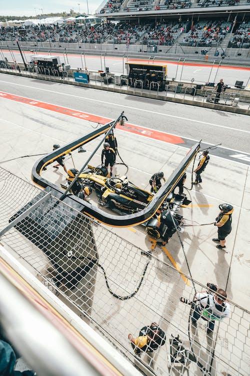 Professional mechanics at pit stop servicing racing car