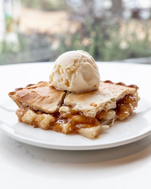 Piece of homemade apple pie served with scoop of vanilla ice cream on plate on white table