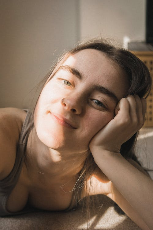 Cheerful young woman resting on floor at home