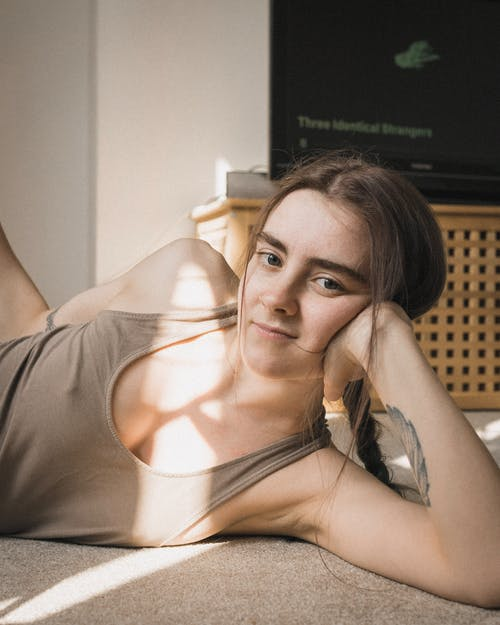 Calm female wearing comfy clothes relaxing on floor in cozy room in rays of sun