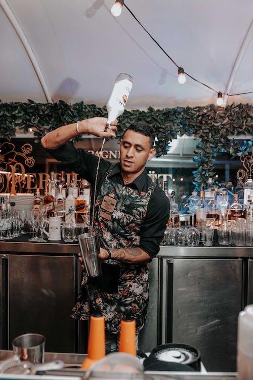 Ethnic bartender pouring drink in shaker
