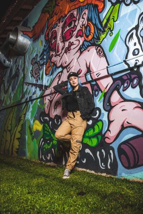 Man in Black Jacket and Brown Pants Standing Beside Wall With Graffiti