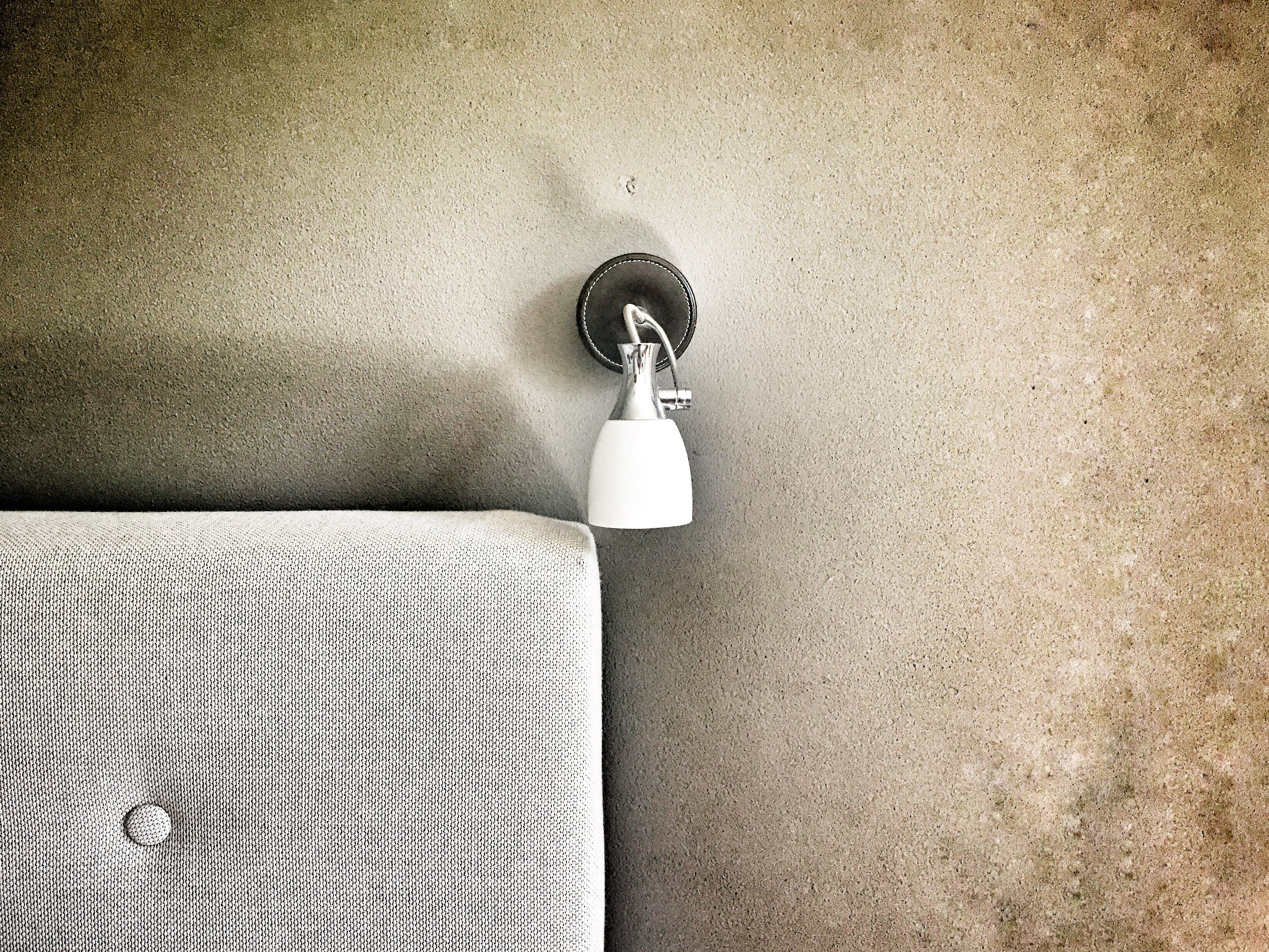 White Sconce Lamp Beside Gray Cushion