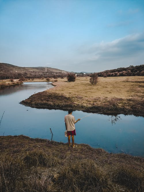 Full body back view of male fisherman in casual clothing standing with fishing rod on shore of calm river in countryside