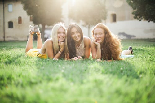 Ground level of cheerful young charming women in summer wear looking at camera while resting on lawn in yard surrounded by building and trees in sunlight