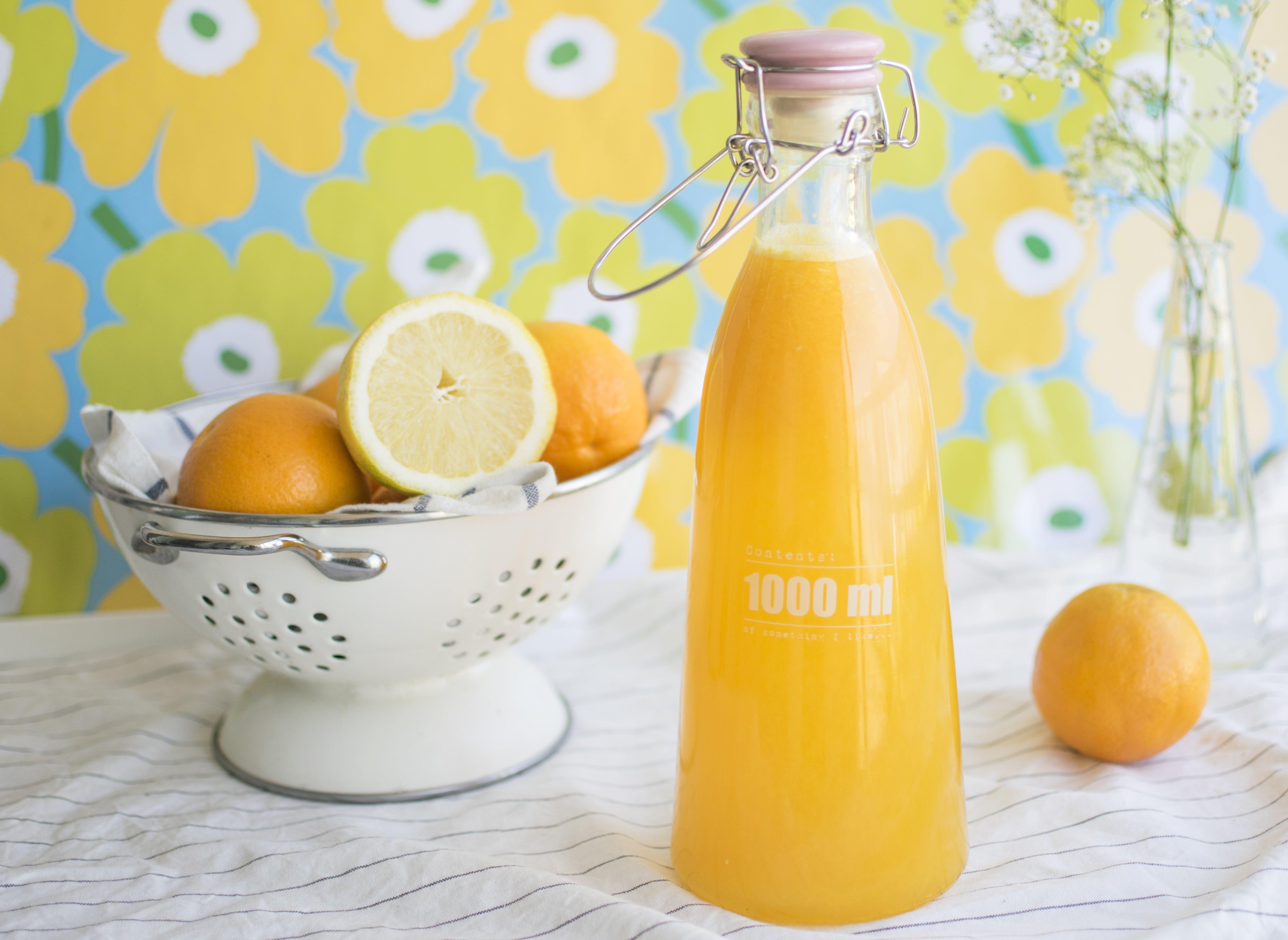 Orange Juice-filled Bottle Near Tray With Orange Fruits