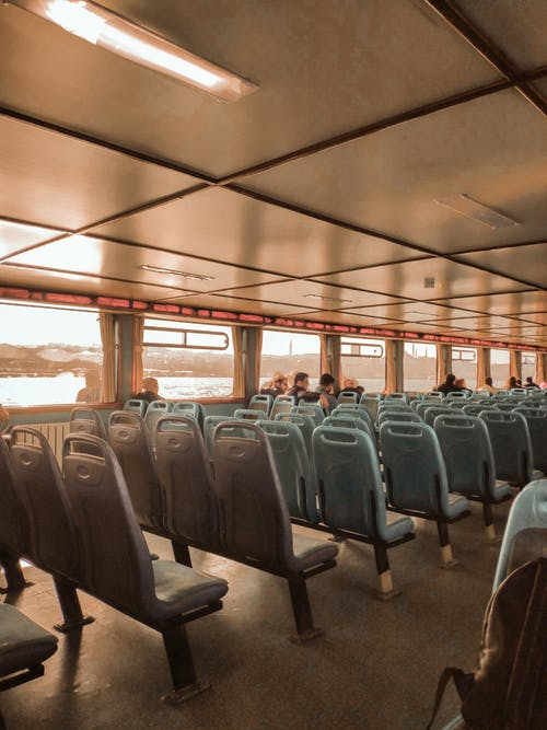 Interior of passenger riverboat with row of grey simple empty seats under ceiling in light of glowing lamps