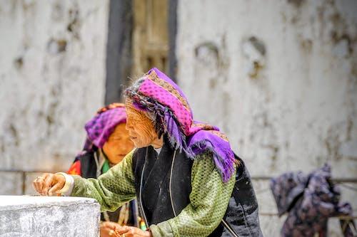 Senior woman sorting seeds on street