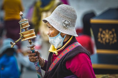 Person in face mask holding Tibetan Buddhist Prayer Wheel