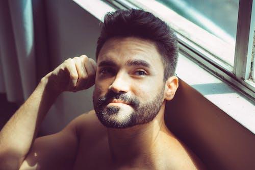 Shirtless man relaxing next to window