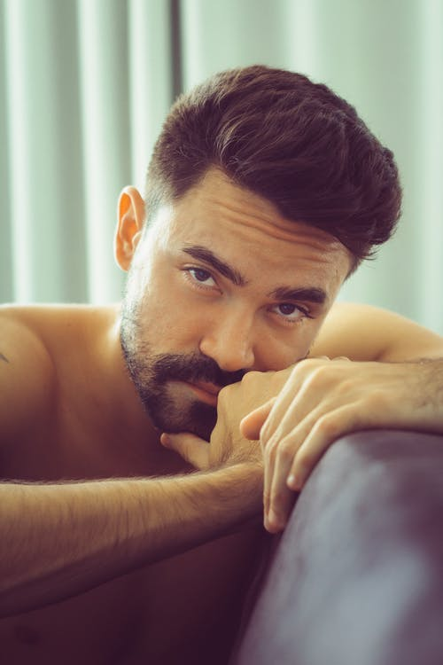 Serious shirtless ethnic bearded male leaning to back of couch and looking at camera while lounging in bright living room decorated with turquoise drapes