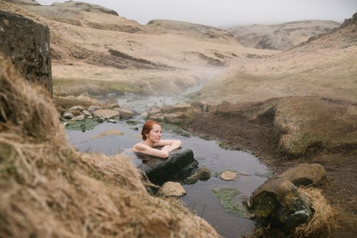 Side view of young red haired female leaning on big stone in pond with transparent water formed of narrow river flow passing between mounts covered with sand in mist
