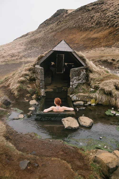 Back view of anonymous red haired lady sitting in stone bath near small house and pond with pure water surrounded by sandy mountain under cloudy sky
