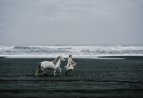 Woman walking with gray stallion on seashore during storm