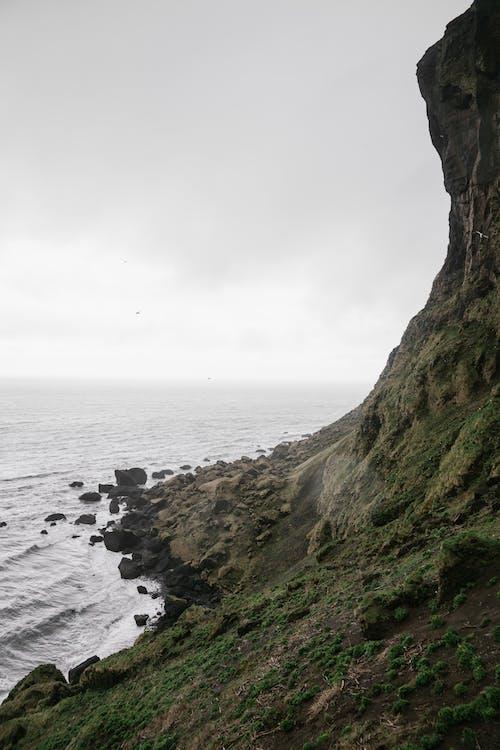 Rocky cliff near sea under cloudy sky