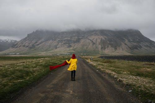 Unrecognizable woman walking on road in mountainous terrain