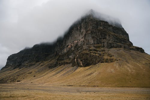Severe massive mountain against cloudy sky