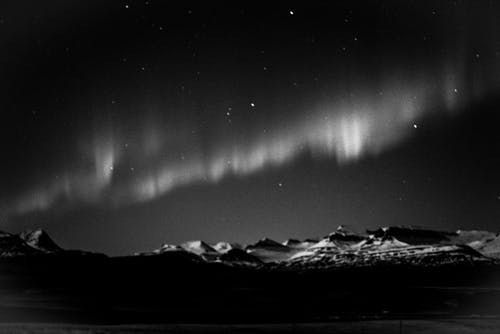 Northern lights over hilly terrain at polar night