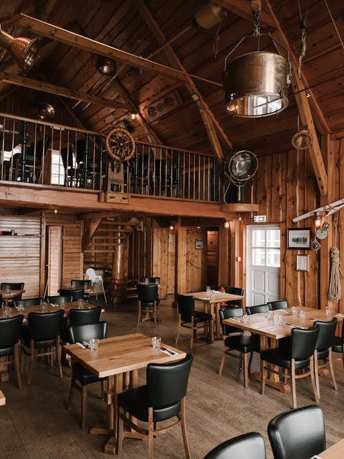 Interior of contemporary restaurant with wooden walls decorated with objects from ancient marine vessels