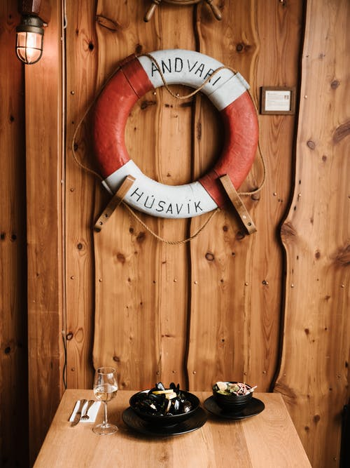 From above of wooden table with various food and glass of wine under lifebuoy placed on wall decorated with lumber