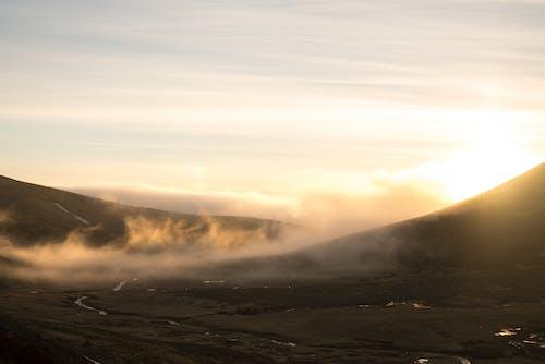 Fog above valley in highlands at sunrise
