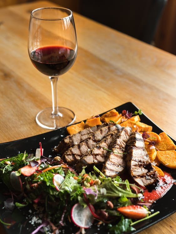 From above of glass of red wine and meat steak pieces served with tomato sauce and potato wedges with vegetable salad placed on ceramic plate on wooden table